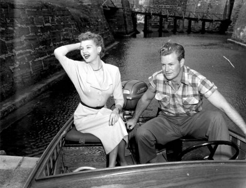 "Mari Aldon and Richard Webb sit on a motorboat when visiting the castle during ""Distant Drums"" premiere: Saint Augustine, Florida"