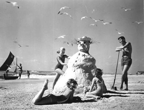 """Three girls making a """"sandman"""" at the beach"""
